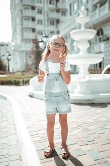 Uliczne jedzenie. poważna mała dziewczynka stoi przed piękną fontanną na ulicy i je swoje lody.