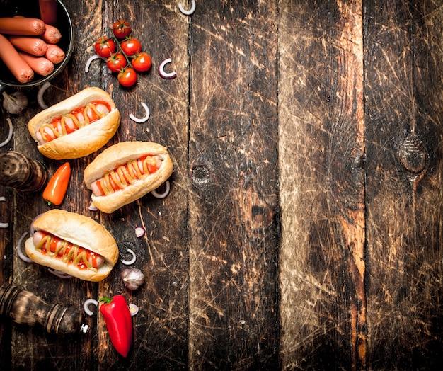 Uliczne jedzenie. świeże hot dogi z papryką, cebulą i pomidorami na drewnianym stole.