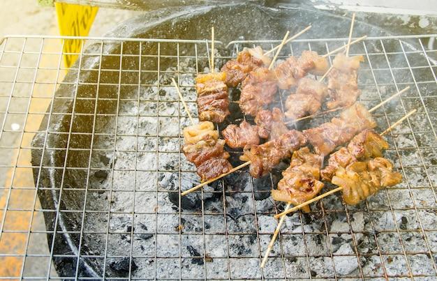 Uliczne jedzenie. wieprzowina z grilla drewniana wtyczka lub pieczone szaszłyki wieprzowe na kuchence