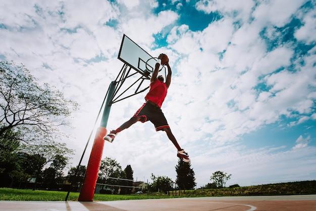 Uliczny koszykarz wykonujący potężny wsad na boisku