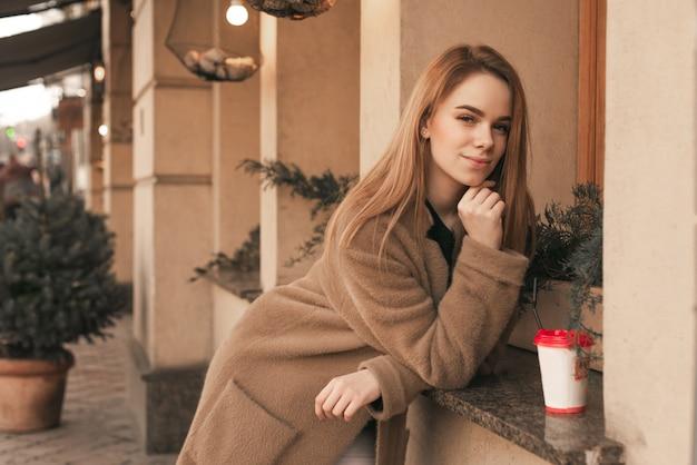 Uliczny portret młodej dziewczyny w płaszczu, stojącej na tle beżowej ściany na parapecie restauracji przy filiżance kawy