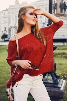 Uliczny portret młodej pięknej eleganckiej kobiety w czerwonym swetrze.