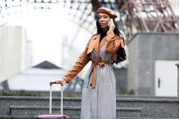 Uliczny portret pięknych kobiet w berecie i płaszczu, podróżujący wygląd, gotowy do podróży, z telefonem i walizką podróżną