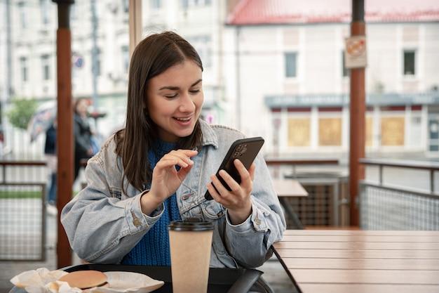 Uliczny portret wesołej młodej kobiety na tarasie kawiarni, trzymającej telefon