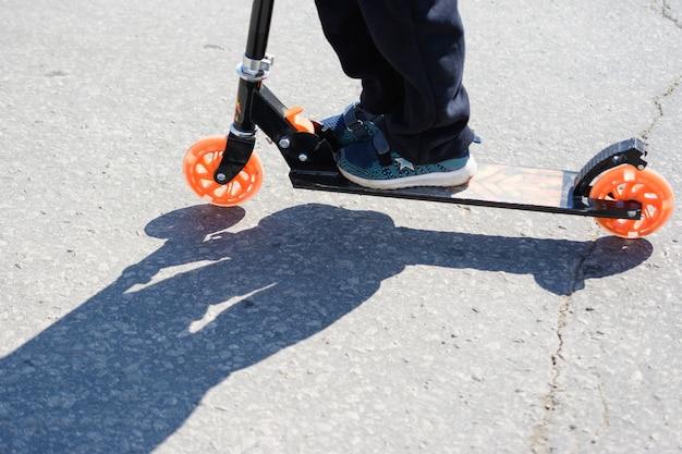 Uljanowsk, rosja-20 kwietnia 2019 r.: dzieci niebezpiecznie jeżdżą skuterami po jezdni. jazda na skuterach. bezpieczeństwo na drodze. niebezpieczne zachowanie pieszych. słoneczny dzień. cienie na chodniku.