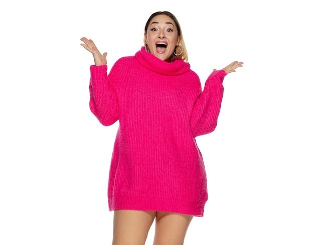 Ulotka. piękna młoda kobieta jasny różowy wygodny sweter, długi rękaw na białym tle na tle białego studia. styl magazynu, moda, koncepcja piękna. modne pozowanie. miejsce na reklamę.