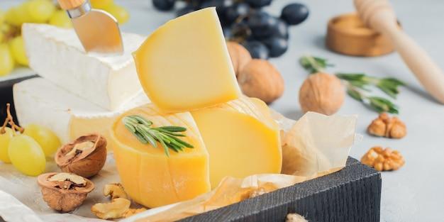Ułóż ser camembert z winogronami, orzechami włoskimi i bazylią na szarym jasnym betonowym lub kamiennym tle. selektywne skupienie.