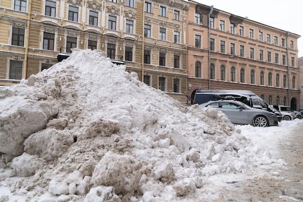 Ułóż stos śniegu z usuniętym po obfitych opadach śniegu na ulicy miasta. zimowa zła pogoda.