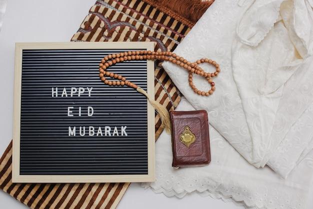Ułożenie muzułmańskiej sukienki zwanej mukena i koralików modlitewnych ze świętą księgą al koranu i tablicą z napisem happy eid mubarak na macie modlitewnej na macie modlitewnej znajduje się litera arabska, co oznacza świętą księgę