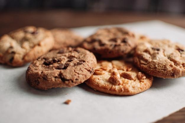 Ułożone ciasteczka czekoladowe na drewnianym stole w stylu rustykalnym, w stylu country. czekoladowi ciastka na ciemnym drewnianym tła zakończeniu up.