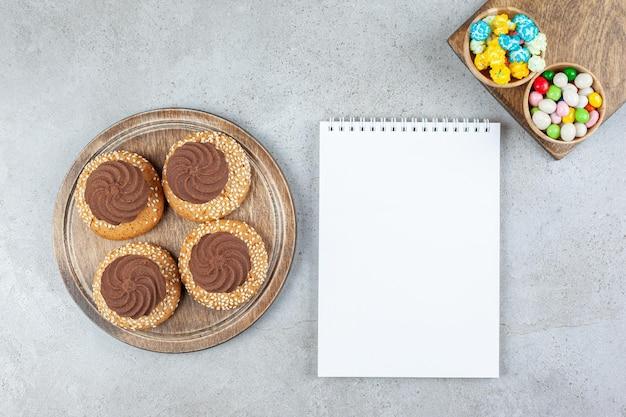 Ułożone ciasteczka i dwie miski cukierków na drewnianych deskach wokół białego notatnika na tle marmuru. wysokiej jakości zdjęcie
