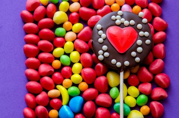 Ułożone kolorowe cukierki z czekoladowym lizakiem w kształcie serca