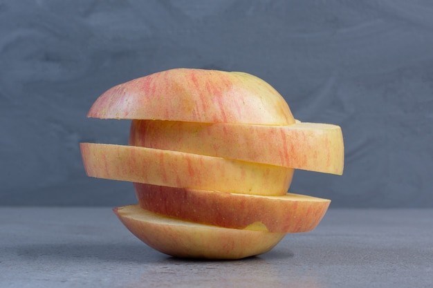 Ułożone plasterki jabłka wyświetlane na tle marmuru.