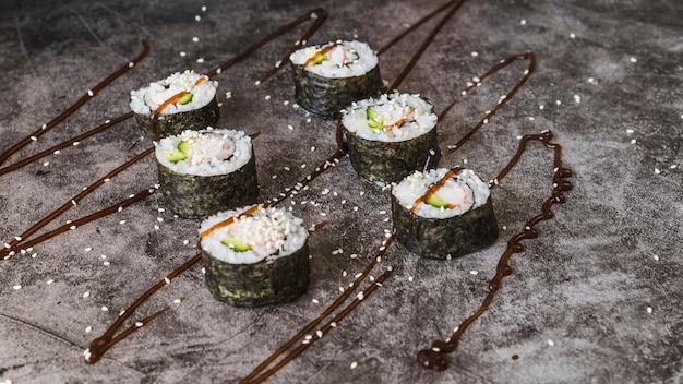 Ułożone rolki sushi z nasionami i sosem