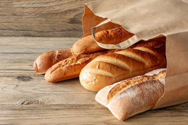 Ułożone różne produkty do pieczenia w papierowej torbie na rustykalnym drewnianym blacie.