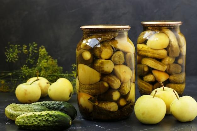Ułożone są marynowane ogórki z jabłkami w słoikach