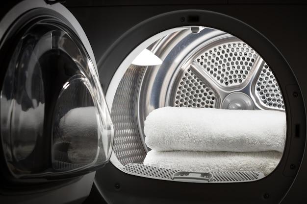 Ułożone w stos czyste białe ręczniki wewnątrz bębna pralki lub suszarki przy otwartych drzwiach