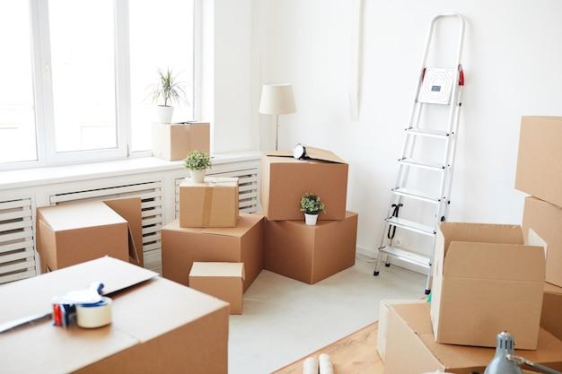 Ułożone w stos pudełka kartonowe w pustym białym pokoju, przeprowadzka, przeprowadzka i koncepcja wystroju domu