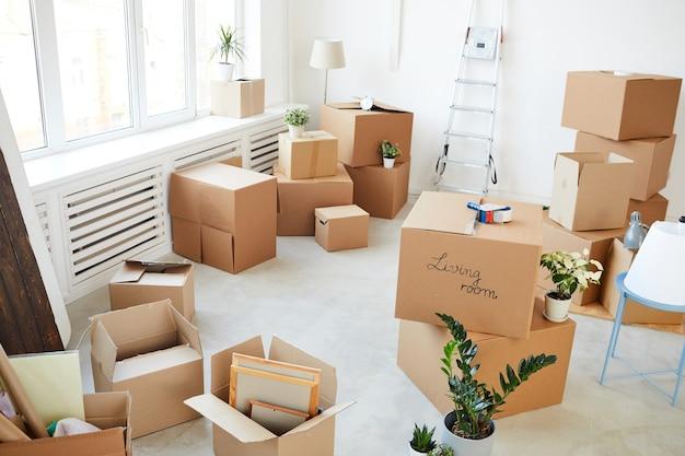 Ułożone w stos pudełka kartonowe w pustym pokoju, przeprowadzka, przeprowadzka i koncepcja wystroju domu