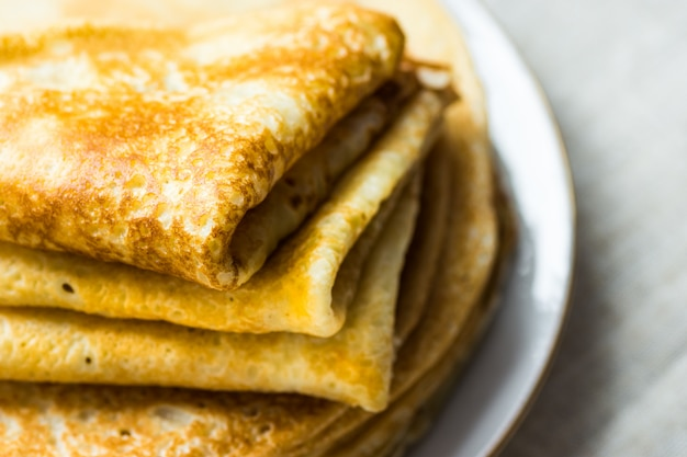 Ułożone złożone naleśniki na białym talerzu na zbliżenie tkaniny lniane, śniadanie