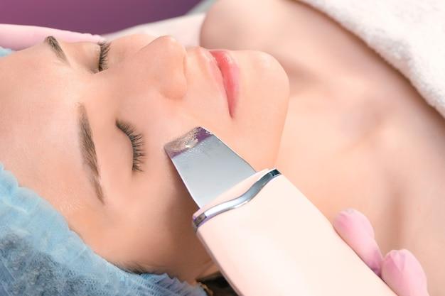 Ultradźwiękowe czyszczenie twarzy młodej kobiety w gabinecie kosmetologicznym.