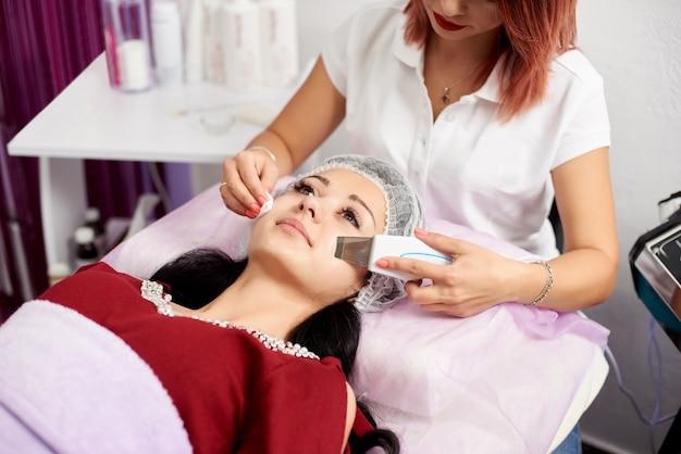 Ultradźwiękowy peeling do skóry. dwie młode kobiety w gabinecie kosmetycznym o stymulującym zabiegu na twarz od terapeuty