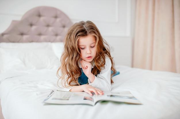 Ulubiona bajka. dziewczyny w łóżku czytają książkę. baw się dobrze w wygodnej sypialni. długie włosy dzieci relaksują się i czytają książkę.