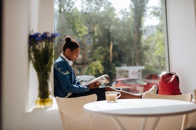 Ulubiona kawiarnia. skoncentrowana brunetka siedząca w pół pozycji na parapecie podczas czytania książki