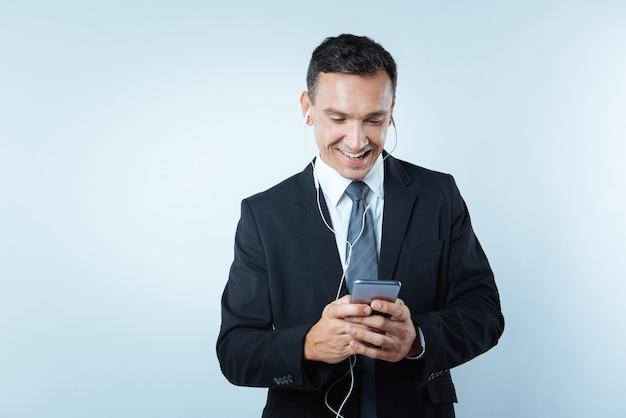 Ulubiona muzyka. szczęśliwy pozytywny zachwycony człowiek ubrany w słuchawki i uśmiechnięty podczas słuchania muzyki