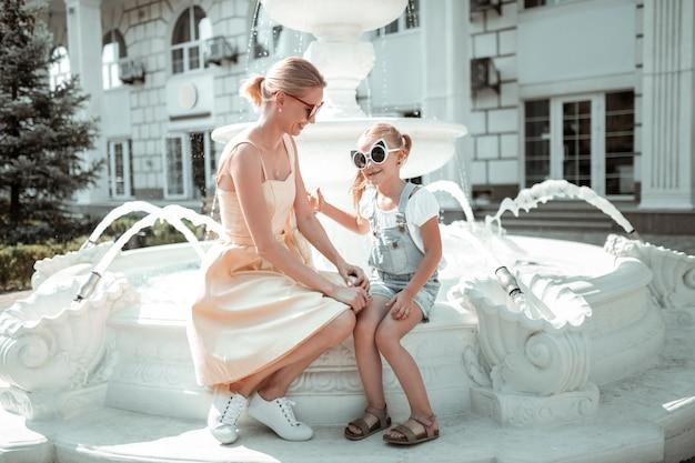 Ulubiona osoba. mała dziewczynka w dużych okularach przeciwsłonecznych siedzi na fontannie spędzając czas z kochającą matką.