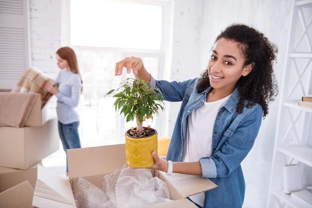 Ulubiona roślina. piękna dziewczyna z kręconymi włosami pozuje z rośliną, podczas gdy jej współlokatorka rozpakowuje koc po przeprowadzce do wspólnego mieszkania