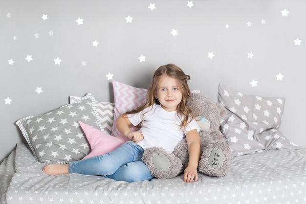 Ulubiona zabawka. dziecko dziewczynka siedzieć na łóżku przytulić misia w jej sypialni. dziecko przygotowuje się do pójścia do łóżka. przyjemny czas w przytulnej sypialni. dziecko bawi się w pokoju dziecięcym zabawką. wystrój pokoju dziecięcego