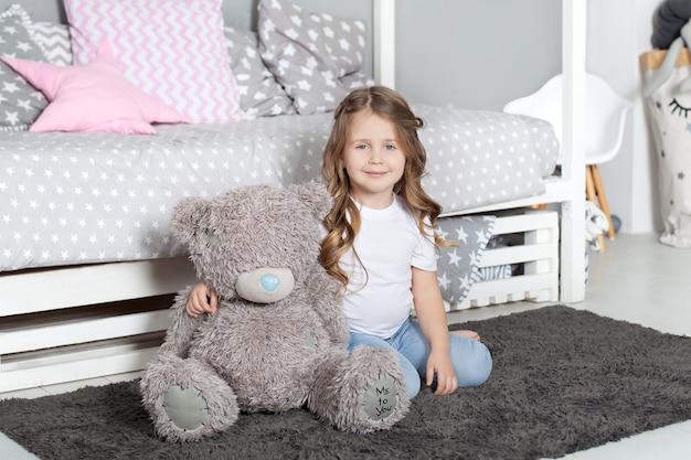 Ulubiona zabawka. dziecko dziewczynka siedzieć na łóżku przytulić misia w jej sypialni. dziecko przygotowuje się do pójścia do łóżka. przyjemny czas w przytulnej sypialni. urocza piżama dla dzieci z długimi włosami, relaksująca i grająca w pluszowe misie.