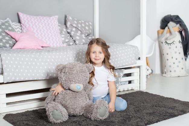 Ulubiona zabawka. dziecko dziewczynka siedzieć na łóżku przytulić misia w jej sypialni. dziecko przygotowuje się do pójścia do łóżka. przyjemny czas w przytulnej sypialni. urocza piżama dla dzieci z długimi włosami, relaksująca i grająca w pluszowe zabawki pluszowego misia.