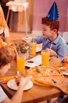 Ulubione jedzenie. przystojne dziecko wyrażające pozytywne nastawienie podczas uroczystej kolacji