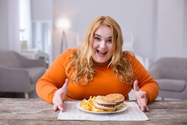Ulubione jedzenie. wesoła kobieta z nadwagą siedzi przy stole i je frytki i kanapki