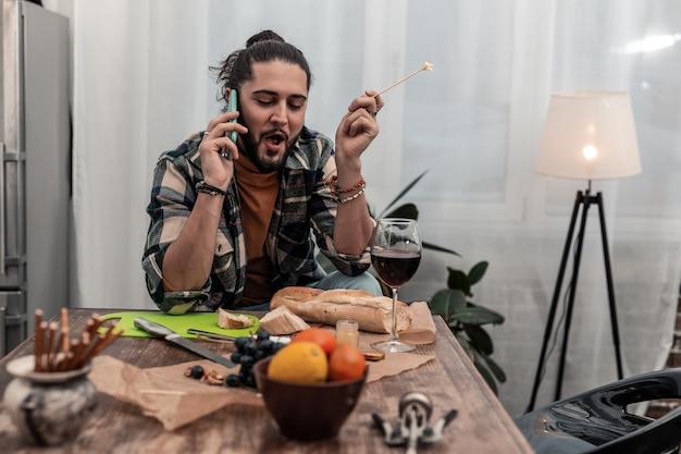 Ulubione jedzenie. zachwycony miły człowiek je smaczną przekąskę podczas rozmowy przez telefon