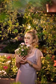 Ulubione kwiaty. ładna, dobrze wyglądająca kobieta ciesząca się pięknymi różami podczas pobytu w ogrodzie