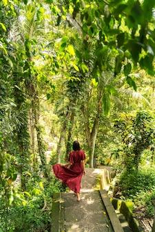 Ulubione miejsce. miła osoba płci żeńskiej z niecierpliwością czekającą na bieganie po schodach po kamiennej ścieżce, egzotyczna przyroda