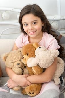 Ulubione zabawki. koncepcja prezent na boże narodzenie. pluszowy miś poprawia samopoczucie psychiczne. dziecko mała dziewczynka figlarny trzymać pluszowego misia pluszowa zabawka. dziecko dziewczynka grać zabawka pluszowego misia tło wnetrze.