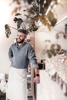 Ulubione zajęcie. pozytywny radosny człowiek cieszący się swoją pracą podczas pracy w stołówce
