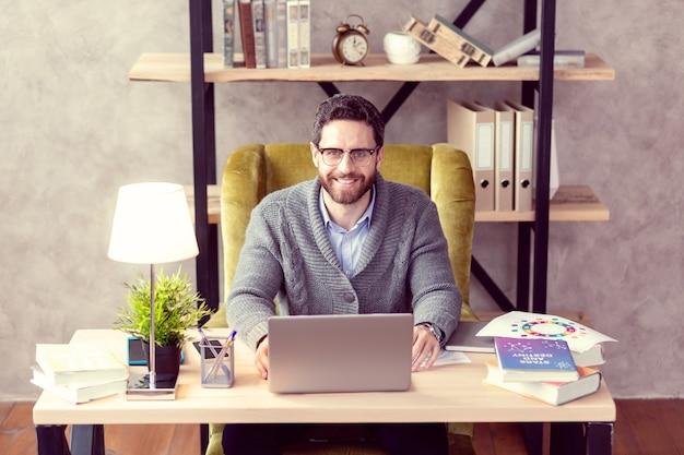 Ulubione zajęcie radosny, wesoły mężczyzna uśmiecha się do ciebie, ciesząc się swoją pracą