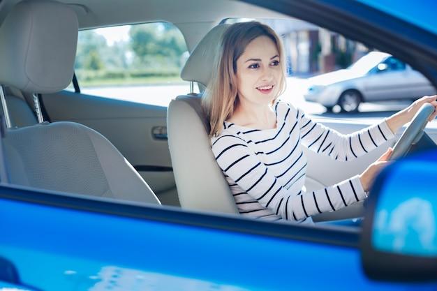 Ulubione zajęcie. szczęśliwa miła przyjemna kobieta siedzi za kierownicą i uśmiecha się podczas prowadzenia samochodu