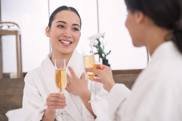 Ulubiony napój. miłe, zachwycone kobiety piją szampana będąc w salonie spa