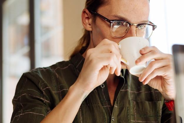 Ulubiony napój. miły, inteligentny człowiek pijący filiżankę kawy, patrząc na ekran laptopa