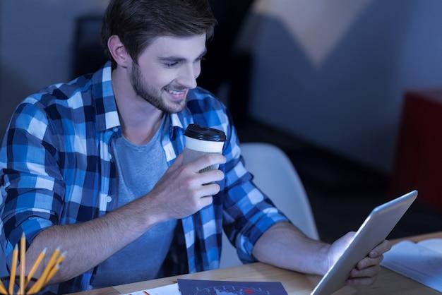 Ulubiony napój. pozytywny radosny zachwycony człowiek czytający wiadomości i cieszący się kawą, jednocześnie bawiąc się
