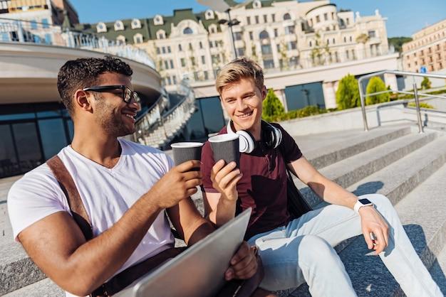 Ulubiony napój. przyjaźni uczniowie wyrażający pozytywne nastawienie i siedzący na schodach w oczekiwaniu na kolegów z grupy