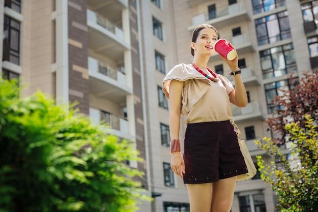 Ulubiony napój. zadowolona miła kobieta uśmiechnięta, ciesząc się jej kawą