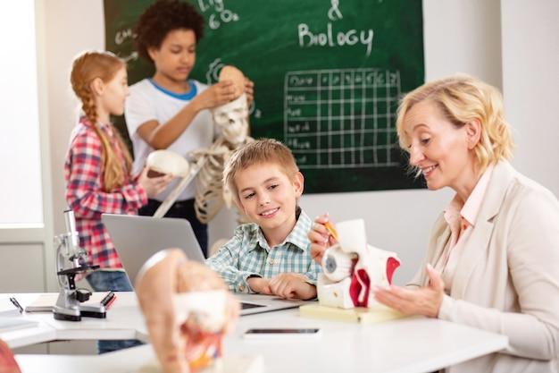 Ulubiony przedmiot. pozytywny słodki chłopiec słucha swojego nauczyciela, a jednocześnie interesuje się anatomią