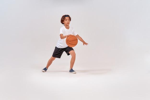 Ulubiony sport pełnometrażowy ujęcie nastoletniego chłopca grającego w koszykówkę, stojąc na białym tle nad